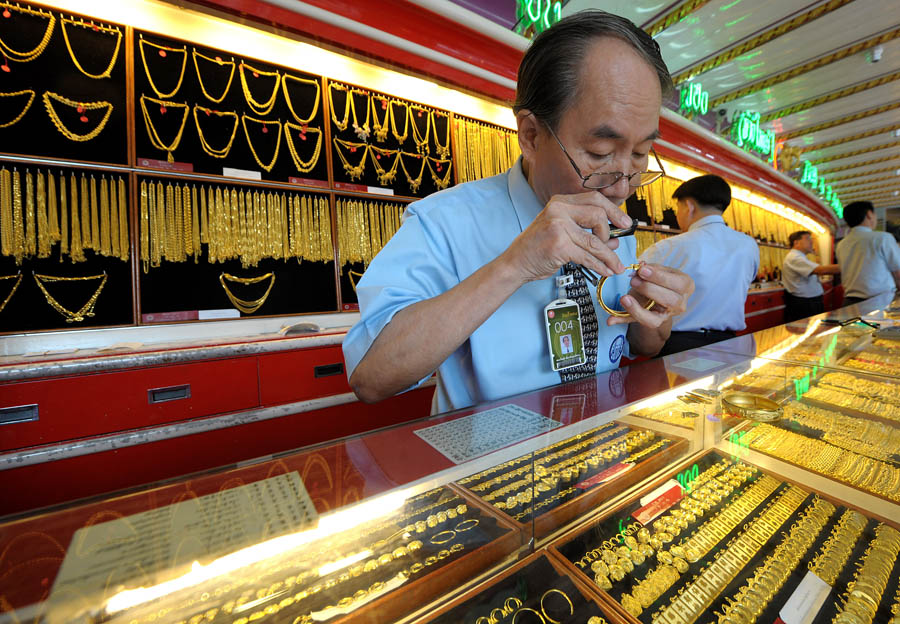 A Thai gold seller inspects a gold brace
